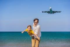 O paizinho e o filho têm o divertimento na praia que olham os planos de aterrissagem Viagem em um avião com conceito das crianças foto de stock