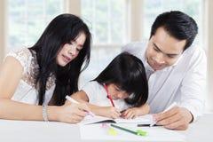 O paizinho e a mamã ajudam sua filha que faz trabalhos de casa Imagem de Stock