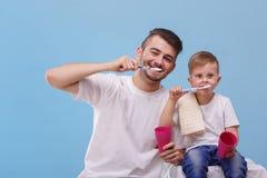 O paizinho e seu filho escovam seus dentes em um fundo azul foto de stock