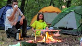 O paizinho e sua filha são fritados em salsichas do fogo vídeos de arquivo