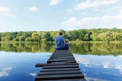 O paizinho e uma menina minúscula nos brins relaxam no rio Vista traseira, fotografia de stock royalty free