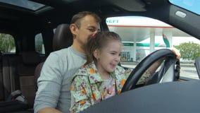 O paizinho ensina a filha conduzir o automóvel no close up do posto de gasolina video estoque
