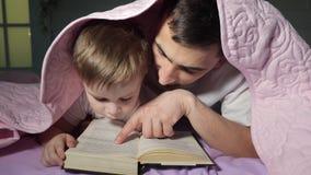 O paizinho ensina seu filho pequeno ler um livro que esconde sob a cobertura filme