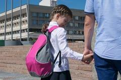 O paizinho está guardando a mão de uma menina com uma trouxa à escola fotografia de stock