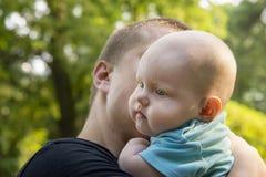 O paizinho está realizando nas mãos seu filho pequeno foto de stock