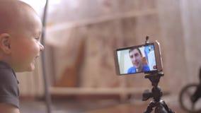 O paizinho fala no skype no telefone com o bebê video estoque