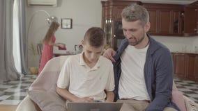 O paizinho farpado considerável e pouco filho estão olhando algo em uma tabuleta ao sentar-se em uma cadeira em casa A mamã limpa filme