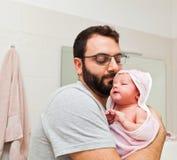 O paizinho guarda sua filha em seus braços após o primeiro banho fotografia de stock royalty free