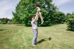 O paizinho joga com sua filha joga-a acima e trava-a Fotos de Stock Royalty Free