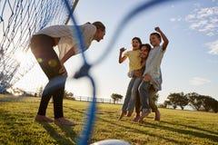 O paizinho levanta seus filho e filha durante um jogo de futebol da família fotografia de stock royalty free