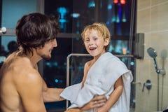O paizinho limpa seu filho com uma toalha após um chuveiro na noite antes de ir dormir no fundo de uma janela com um panorâmico fotografia de stock royalty free