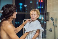 O paizinho limpa seu filho com uma toalha após um chuveiro na noite antes de ir dormir no fundo de uma janela com a fotografia de stock