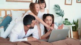 O paizinho, a mamã e duas filhas jogam no jogo de computador no portátil, movimento lento filme