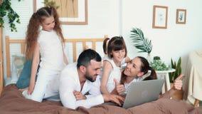 O paizinho, a mamã e duas filhas jogam no jogo de computador no portátil, movimento lento video estoque