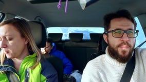 O paizinho, a mamã e o filho da família comem no sanduíche do carro e no café da bebida video estoque