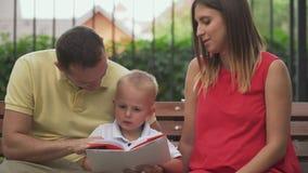O paizinho, a mamã e o filho estão lendo um livro em um banco de parque filme