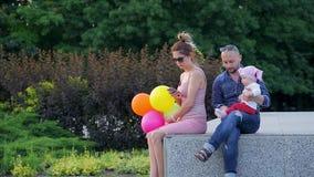 O paizinho novo com a filha infantil bonito senta-se na borda concreta, perto da mamã senta-se e está conversando no telefone no  filme