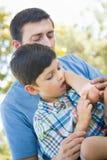 O paizinho põe uma atadura sobre o cotovelo de seu filho novo imagem de stock