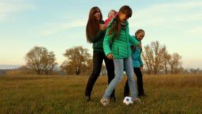 O paizinho retrocede a bola de futebol Crianças e futebol do jogo da mamã no campo Família que joga com a criança pequena pela bo fotos de stock