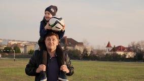 O paizinho salta com seu filho pequeno nos ombros ao jogar o movimento lento do futebol fora filme
