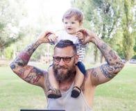 O paizinho Tattooed tem o divertimento com seu filho Foto de Stock