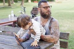 O paizinho Tattooed tem o divertimento com seu filho Foto de Stock Royalty Free