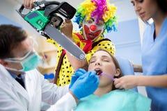 O palhaço ameaça a menina com a serra de cadeia em ambulante dental fotos de stock