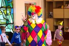 O palhaço colorido engraçado no jardim de infância mostra o sinal, vitória, Retrato Foto de Stock