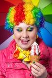 O palhaço com arco-íris compo comer o gelado Fotos de Stock