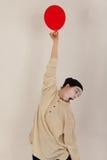 O palhaço está jogando com balões vermelhos Fotos de Stock