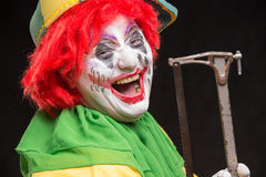 O palhaço mau assustador com um sorriso feio e viu em um backgroun preto Imagens de Stock