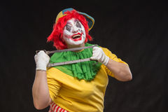 O palhaço mau assustador com um sorriso feio e viu em um backgroun preto Imagens de Stock Royalty Free