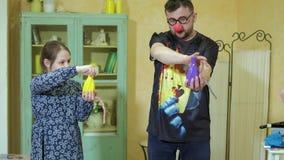 O palhaço mostra à menina um truque com garrafas mágicas e uma corda 4k vídeos de arquivo