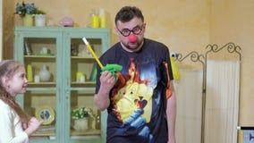 O palhaço mostra à menina um truque com uma varinha mágica e um saco 4k video estoque