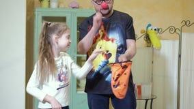 O palhaço mostra à menina um truque com uma varinha mágica e um saco 4k vídeos de arquivo