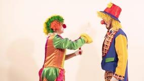 O palhaço novo feliz rega o pulverizador de bolhas de sabão sobre um outro palhaço de circo filme