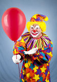 O palhaço oferece o balão Fotos de Stock