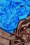 O pano de seda azul e marrom do cetim de dobras onduladas texture o fundo Foto de Stock