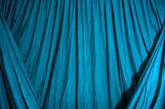 O pano preto drapejado do fundo iluminou-se com gel azul fotografia de stock royalty free