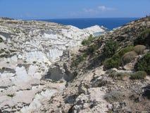 O panorama das rochas brancas da lua costeia com floresta do mediteranea e na distância um mar azul da ilha dos Milos em Grécia Foto de Stock