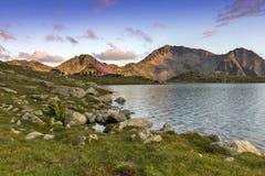 O panorama do por do sol sobre o lago Tevno e Kamenitsa repicam, montanha de Pirin imagens de stock royalty free