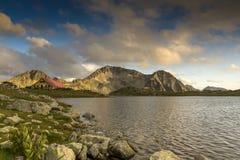 O panorama do por do sol sobre o lago Tevno e Kamenitsa repicam, montanha de Pirin imagem de stock