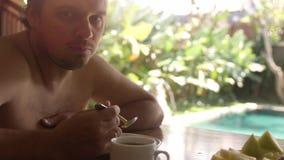 O papa de aveia antropófago considerável novo da aveia tem o café da manhã que senta-se em sua casa de campo na piscina no fundo  filme