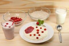 O papa de aveia com morangos silvestres, batido do leite do arroz e ingredien Imagem de Stock