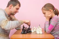 O papa faz seu próximo passo ao jogar a xadrez com sua filha Imagens de Stock Royalty Free