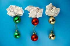 O papel amarrotado e da árvore de Natal bolas estão em um fundo azul imagem de stock