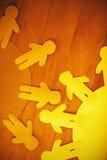 O papel azul e amarelo cortou figuras na tabela de madeira Foto de Stock Royalty Free