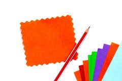 O papel da cor para o origâmi encontra-se com um fã, uma folha de papel alaranjada com uma borda ondulada, um lápis molde fotografia de stock