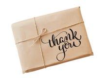 O papel de embalagem do envelope amarrado com corda em um fundo branco e o texto agradecem-lhe Tração da mão da rotulação da cali Fotografia de Stock Royalty Free
