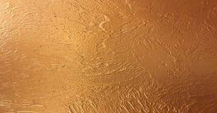 O papel de fundo do ouro, textura é vintage velho cor afligida do ouro maciço com pintura áspera do grunge da casca em bordas imagem de stock